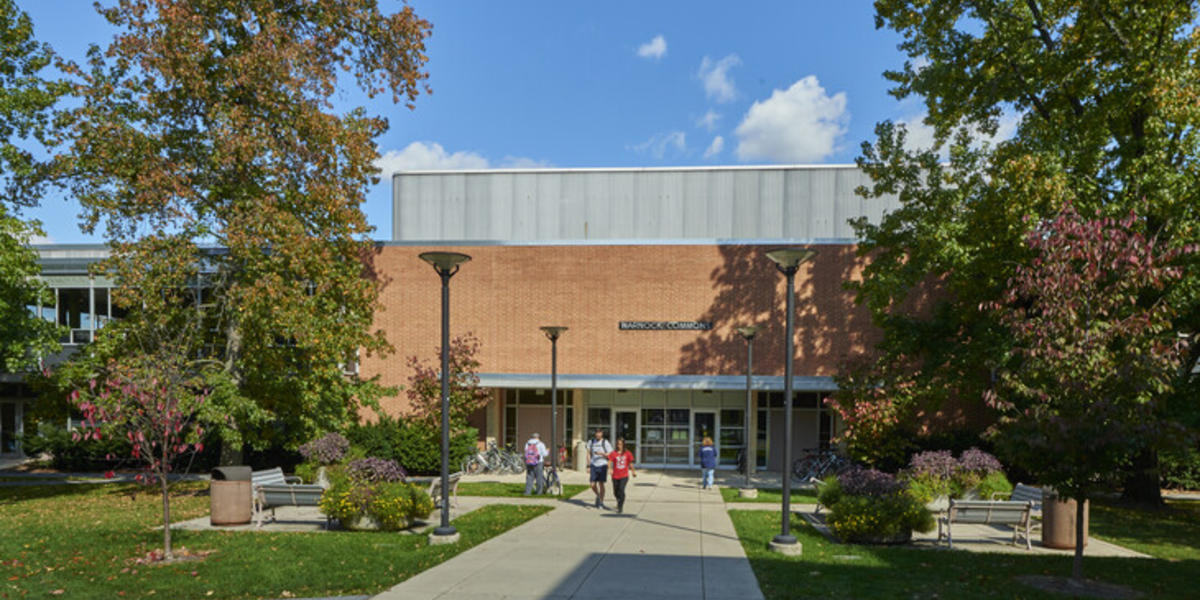 Students walking outside of Warnock Commons on a fall afternoon.