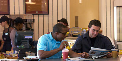 Two males students in a retail dining location.