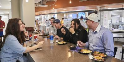 Students eat at a community table in East Food Distrist all-you-care-to-eat dining commons