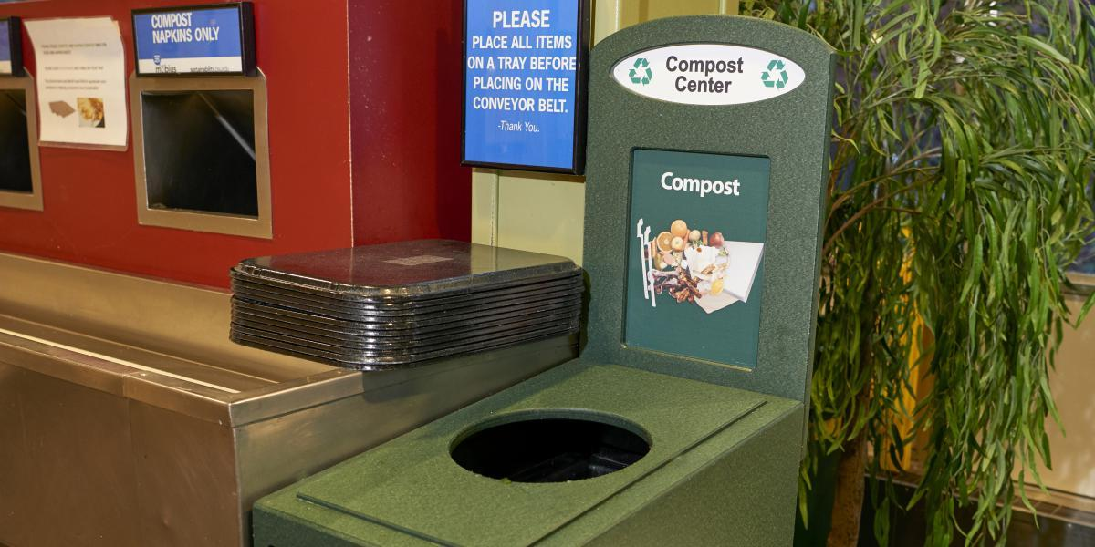 A green composting bin sits next to a conveyor belt.