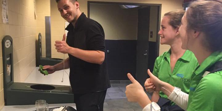 Eco Reps give thumbs up to student cleaning plates into composting bin