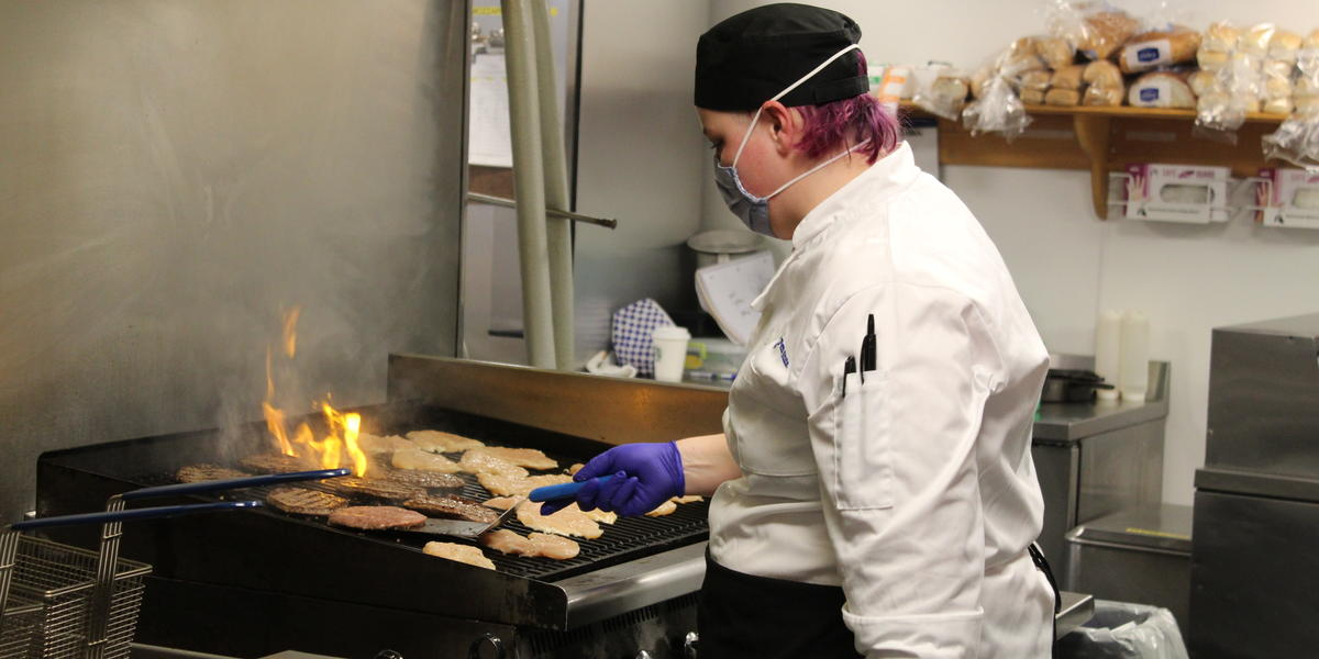 Sarah Graham, food preparer, grills up chicken and burgers at the new Market North in Warnock Commons, at University Park.